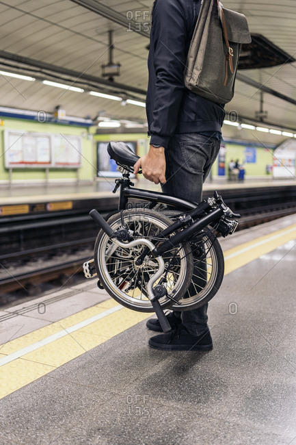 Unrecognized man in the metro holding his detachable bike.