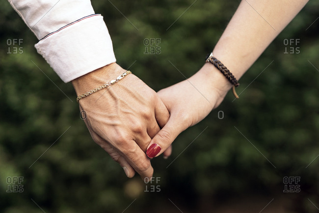 Unrecognized couple having romantic moment and holding hands.