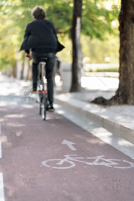 Unrecognized man riding his bike following bike trail.