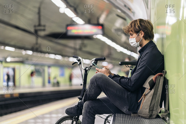 Young man sitting in the metro next to his detachable bike.