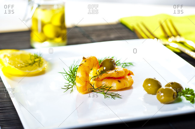 Cooked shrimp with olives on plate