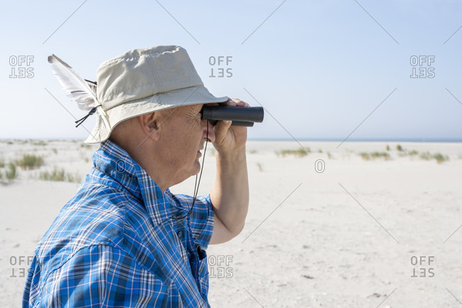 Germany, Lower Saxony, East Frisia, Juist, man watching birds on the beach.