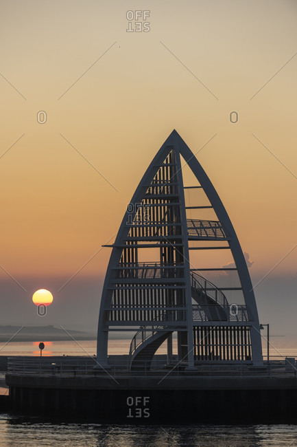 Germany, Lower Saxony, East Frisia, Juist, sunrise mood at the port entrance with the sea mark (17 m high steel structure).