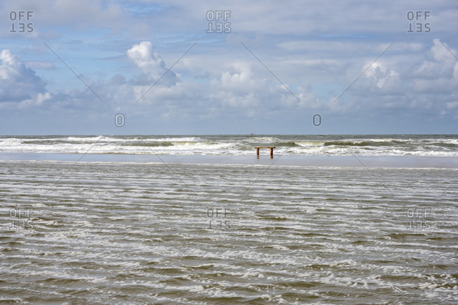 Germany, Lower Saxony, East Frisia, Juist, lonely bench on the beach at high tide.