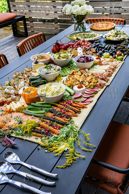 Grazing Board with Charcuterie, Tarts, Fruits and Vegetables on Table in Outdoor Setting
