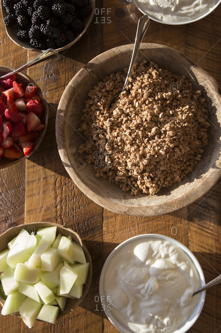 High Angle View of Bowls of Granola, Yogurt and Fresh Fruit on Wood Table