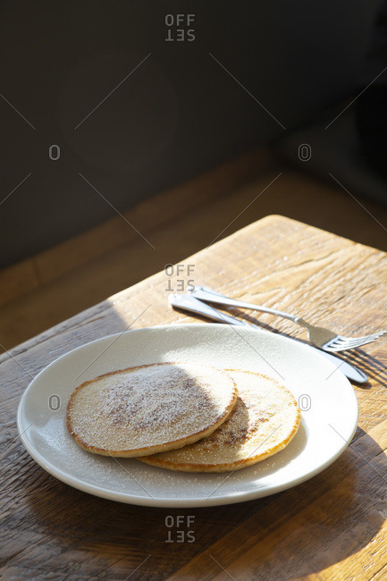 Two Pancakes with Powdered Sugar on Plate