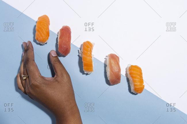 Hand reaching for a piece of Nigiri
