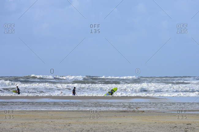 September 5, 2019: Germany, Lower Saxony, East Frisia, Juist, surfers in stormy weather on the beach.