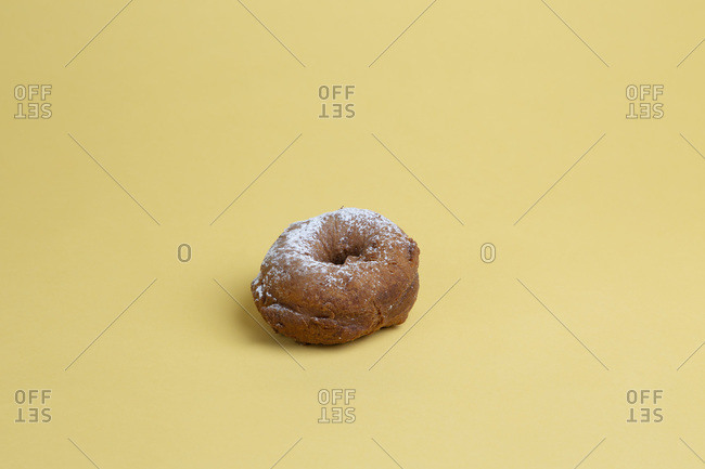 Doughnut with Powdered Sugar on Yellow Background
