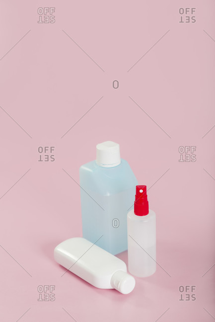 Disinfectant bottles on a pink background