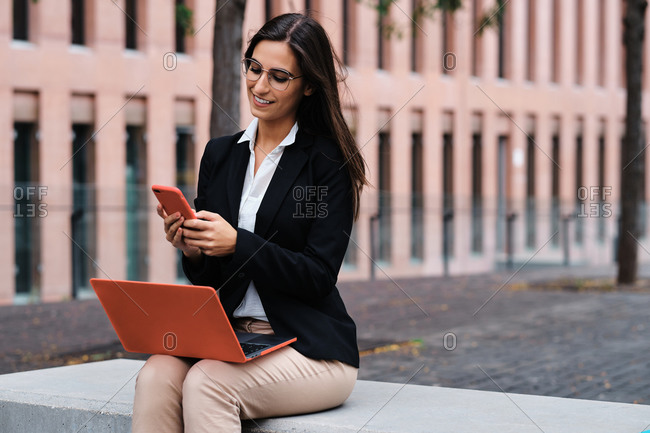 Delighted woman sitting on bench in city and working on business project while using smartphone and laptop computer