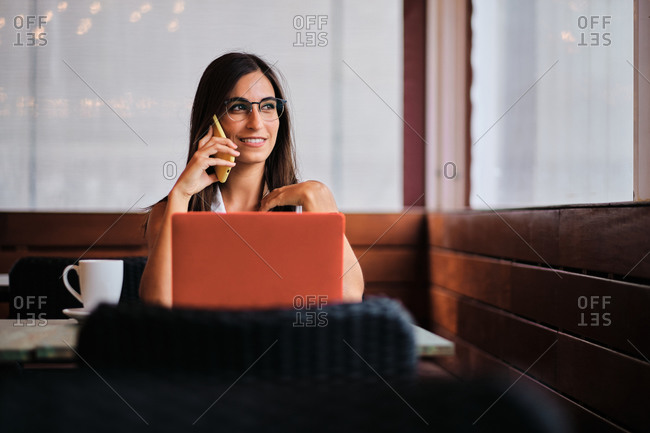 Delighted female entrepreneur working remotely in cafe while discussing business issues on smartphone and sitting at table with laptop