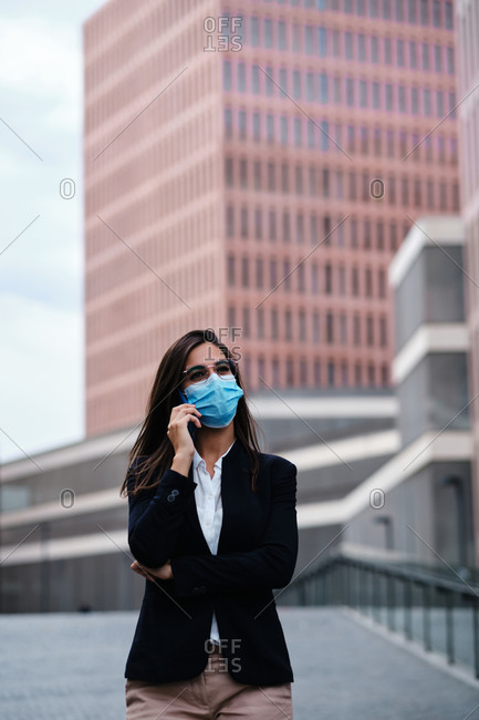 Busy female entrepreneur in formal wear and medical mask walking along street in city and talking on smartphone while discussing work issues and looking away during coronavirus pandemic