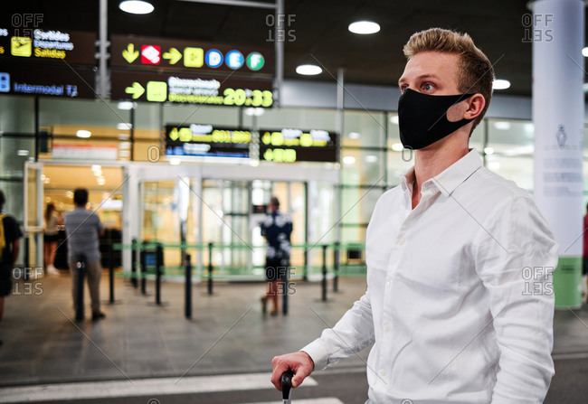 Serious male wearing protective mask standing in departure lounge of airport and waiting for flight during coronavirus epidemic while looking away