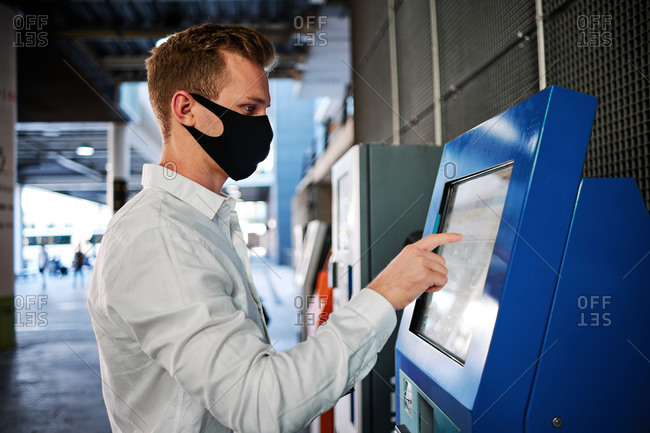 Side view of male wearing protective mask using modern self service terminal and touching display during coronavirus epidemic