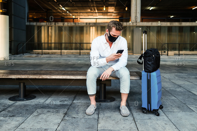 Calm male tourist in protective mask and with luggage sitting on bench in airport and using smartphone before departure during coronavirus pandemic
