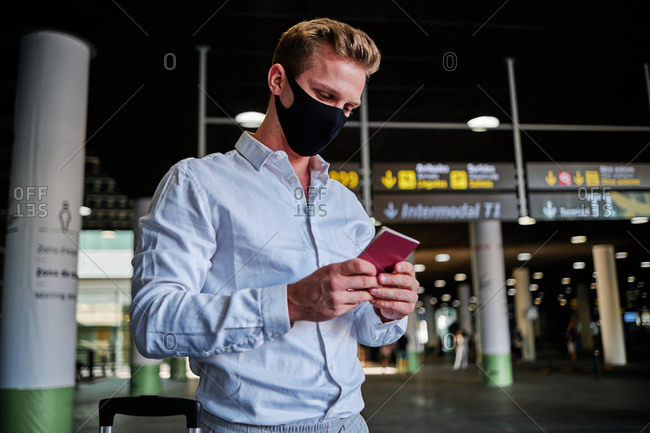 Low angle of male tourist in protective mask standing with passport in departure lounge of airport and looking away while waiting for flight