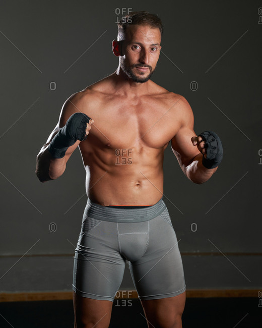 Brutal shirtless sportsman with muscular body preparing to fight standing looking at camera against grey background