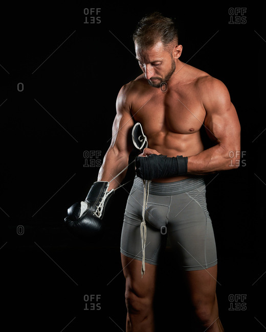 Brutal shirtless sportsman with muscular body putting on and adjusting boxing gloves while preparing to fight against black background