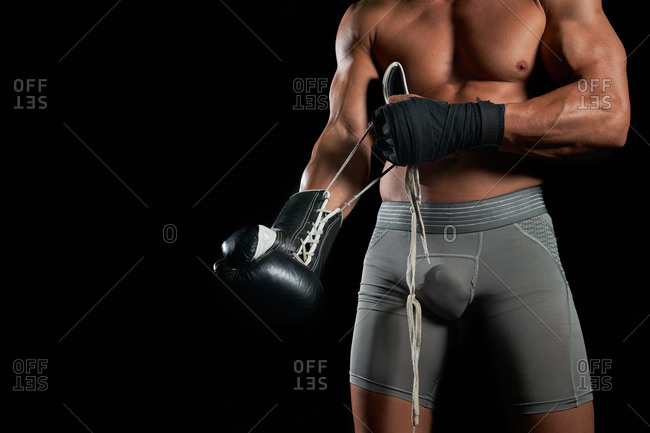 Cropped unrecognizable brutal shirtless sportsman with muscular body putting on and adjusting boxing gloves while preparing to fight against black background