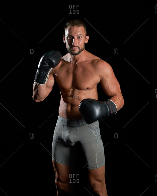 Brutal shirtless sportsman with muscular body with boxing gloves while preparing to fight standing looking at camera against black background
