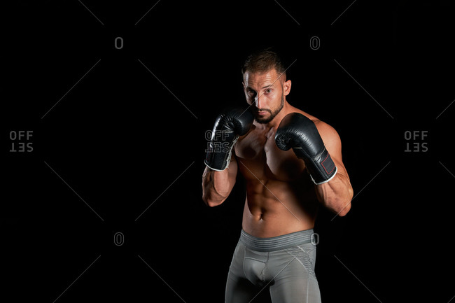 Confident muscular shirtless man in boxing gloves attacking and punching during kickboxing workout against black background