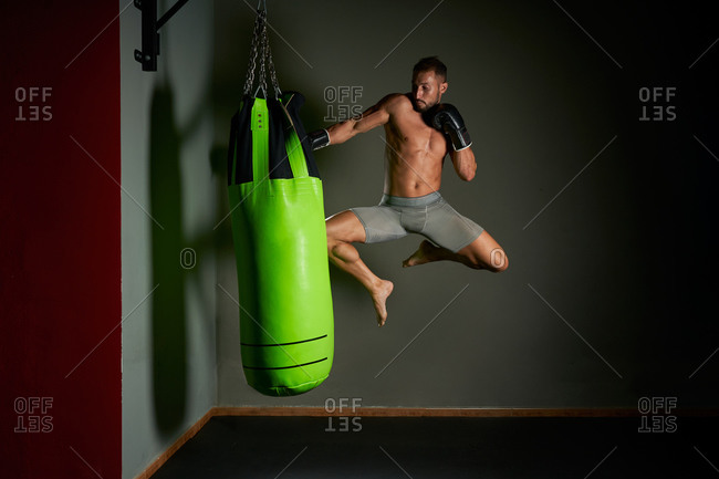 Full length of enduring shirtless male kickboxer in boxing gloves performing knee strike and punches while exercising with heavy punching bag