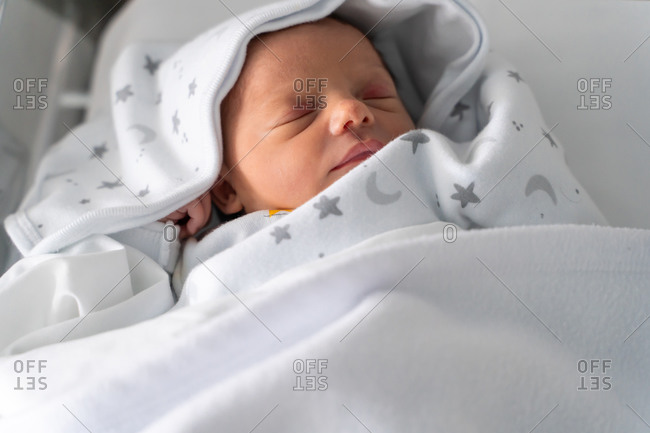 From above close up view of adorable tiny newborn child wrapped in blanket sleeping peacefully in crib