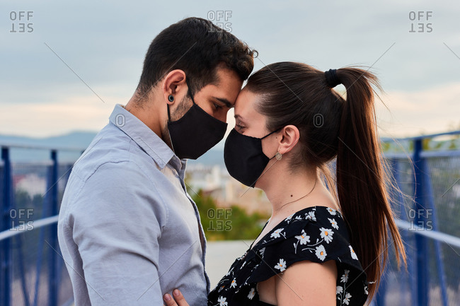Side view of gentle couple wearing protective masks embracing with closed eyes while touching foreheads and standing on bridge in city during coronavirus epidemic