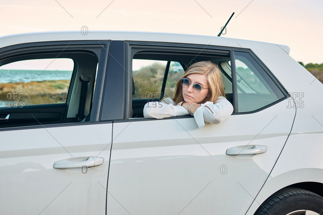 Side view of delighted female sitting in car and traveling along seaside in summer while looking away
