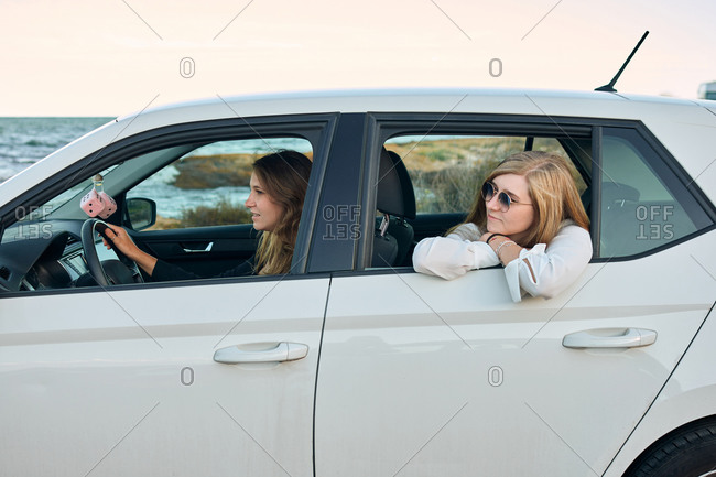Side view of delighted female friends sitting in car and traveling along seaside in summer while looking away