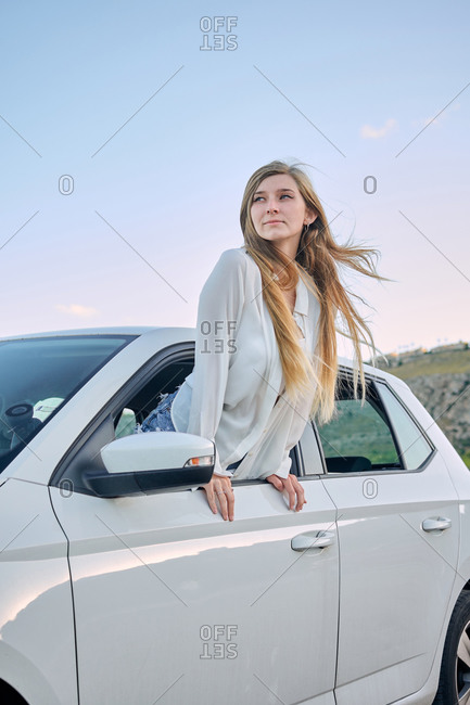 Carefree female driver looking out of window of automobile and enjoying fresh air in nature during summer vacation in evening while looking away