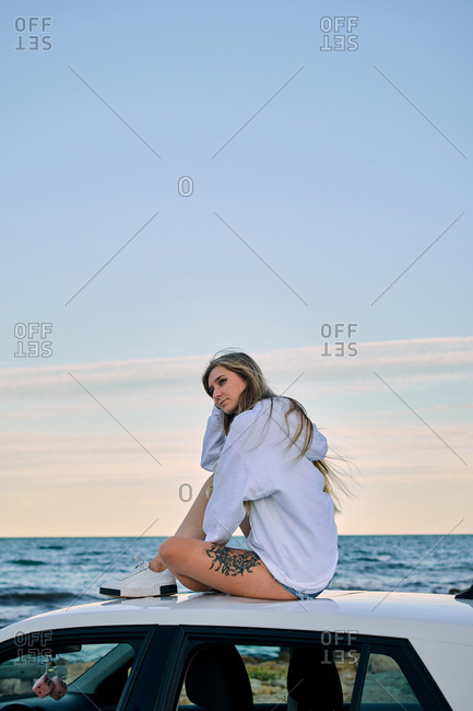 Side view of serene female traveler sitting on car roof and enjoying sunset in evening on background of sea in summer during vacation