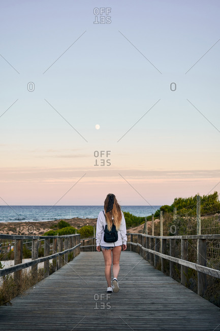 Back view of female tourist on wooden embankment at seaside and enjoying freedom during summer vacation