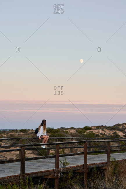 Side view of unrecognizable female tourist sitting on wooden fence on embankment and admiring peaceful sunset over sea in summer