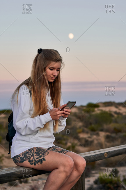 Calm female traveler sitting on wooden fence on promenade and messaging on social media via cellphone while relaxing at sundown in summer