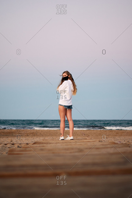 Back view of female tourist wearing protective mask standing on sandy beach near sea against sunset sky and looking over shoulder during coronavirus epidemic