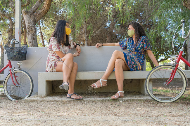 Full length of positive multiracial girlfriends in summer dresses and protective masks sitting on bench near bicycles and chatting happily while spending summer day together in park