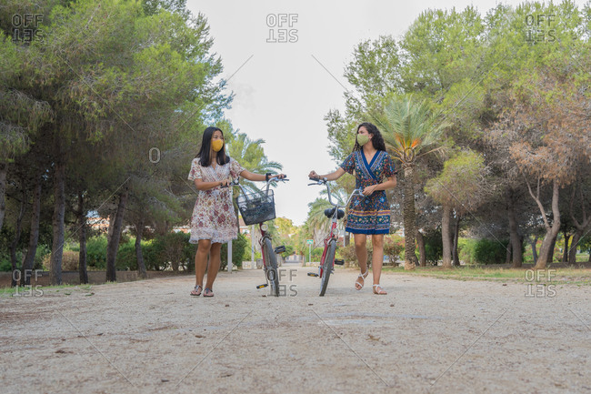 Full length of delighted young female friends in dresses having fun while walking with bicycles on path in tropical park during summer holidays together