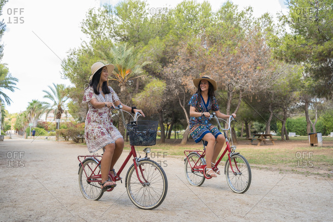Full length of delighted young female friends in dresses and hats having fun while riding bicycles on path in tropical park during summer holidays together