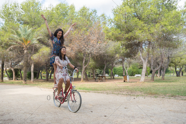 Side view of happy playful multiracial girlfriends in summer dresses riding bike together while having fun and enjoying summer weekend in park