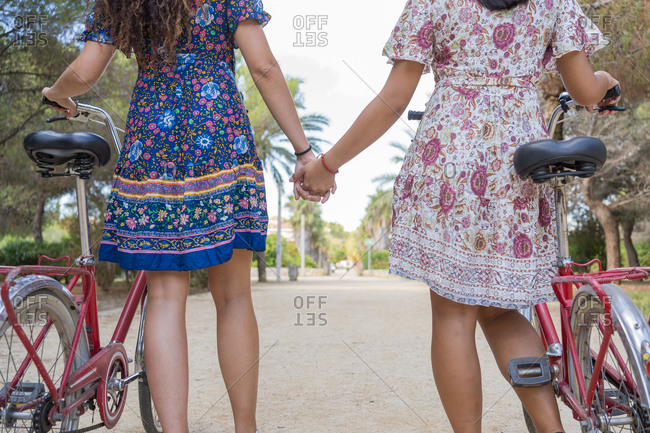 Back view of crop anonymous young female friends in colorful dresses holding hands while standing with bikes on pathway in green tropical park during summer holidays