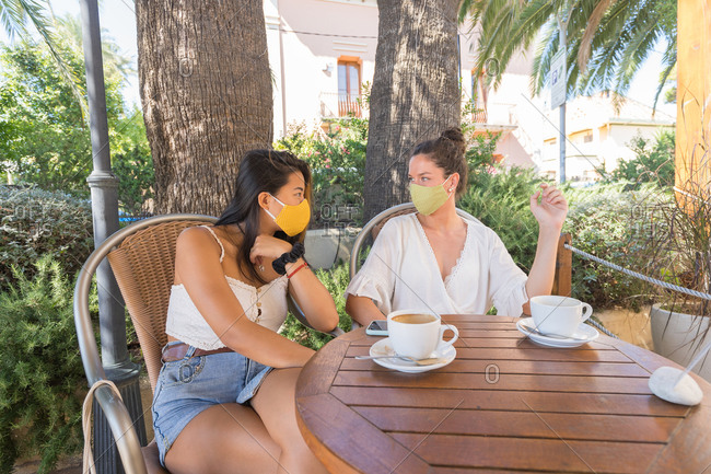 Multiethnic girlfriends in protective masks sitting at table with cups of hot drinks and talking while spending summer day together in outdoor cafeteria with tropical trees