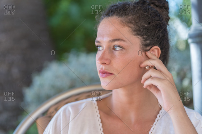 Sensual young female in white blouse looking at camera while sitting in wicker chair against blurred green trees