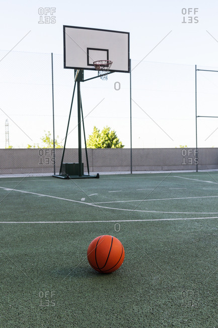 Orange ball for basketball placed on modern sports ground on sunny day in summer