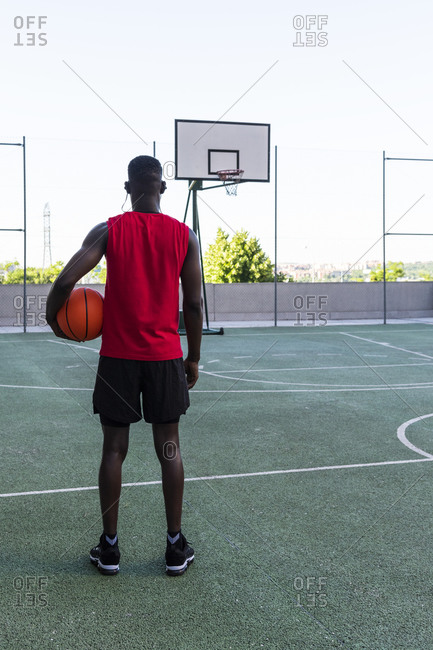 Back view of African American male player in sportswear standing with basketball on playground and looking away