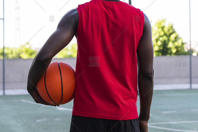 Back view of cropped unrecognizable African American male player in sportswear standing with basketball on playground and looking away