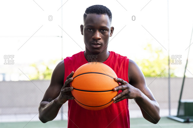 Determined male basketball player standing with ball on playground in summer and looking at camera