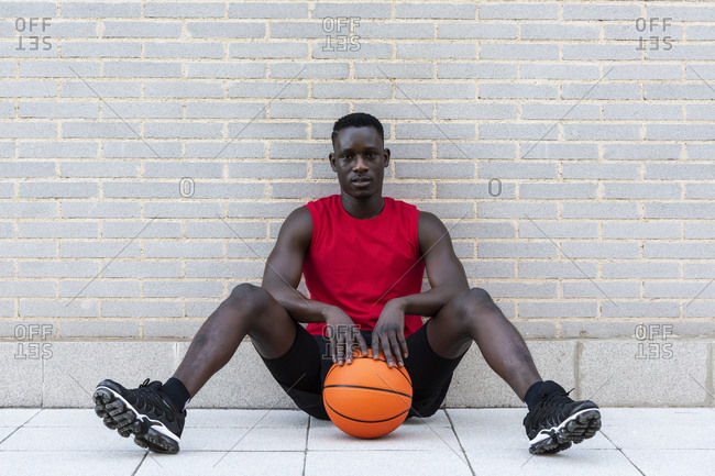 Confident African American male basketball player in sportswear sitting with ball on stone border on playground and looking at camera